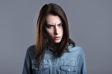 choleric: Anger. Furious young woman standing against grey background and looking at you