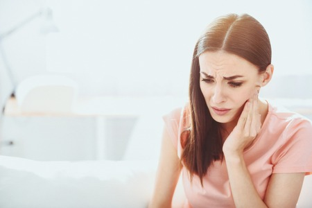 Unstoppable pain. Beautiful brunette woman grimacing and touching her jowl while having toothache. Stock Photo