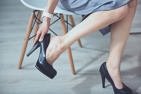 Unsuitable shoes. Young slim woman sitting on the chair and taking off hills Stock Photo
