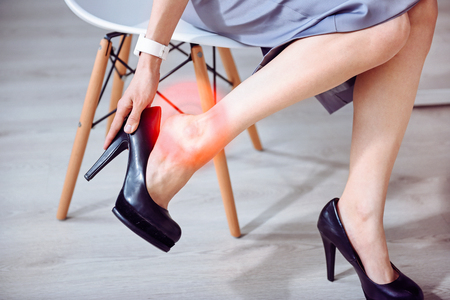 I hate hills. Close up of young slim woman sitting on the chair and having pain in the legs while taking off her shoes. Stock Photo