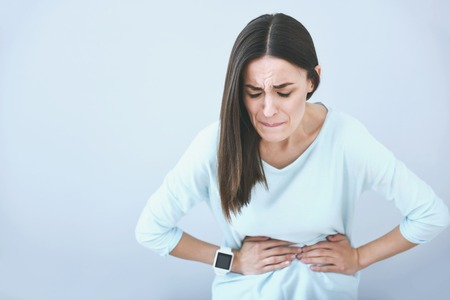 sudden: Sudden pain. Brown haired young woman biting her lip and putting arms on her belly while standing against white isolated background.