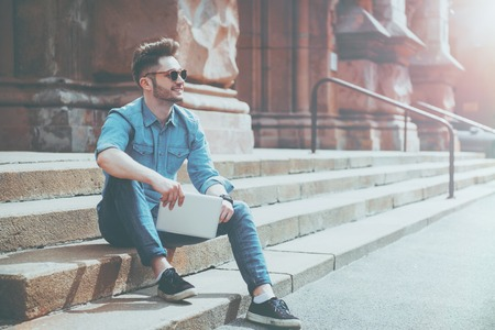 gladness: Live life bright. Cheerful content smiling man holding tablet and expressing gladness while resting on the footsteps