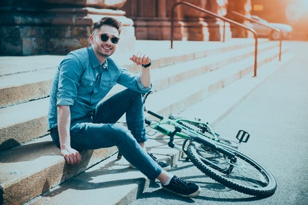 Ready to ride. Cheerful handsome smiling young man sitting on the footsteps near his bicycle and resting while sharing positive emotions