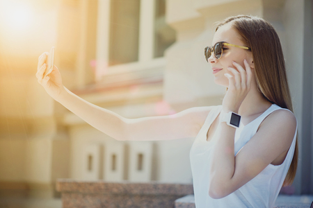Breath of beauty. Delighted cheerful smiling womna holding smart phone and making selfies while having a walk