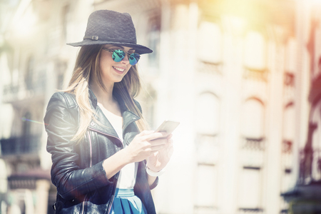 gladness: Full of positivity. Cheerful content smiling young woman using cell phone and expressing gladness while walking