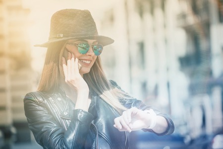 What time is it. Positive charming young trendy woman looking at her smartwatch and walking while talking on cell phone Stock Photo