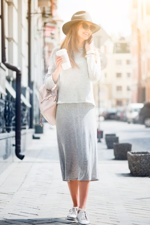 womna: Get urbanized. Cheerful delighted young womna walking in the street and drinking coffee while talking on cell phone Stock Photo