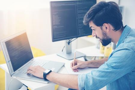 それに注意してください。何かを指摘しながらオフィスでプログラマーとして働いてラップトップ上でコーディング ハンサムな若い男を集中してく