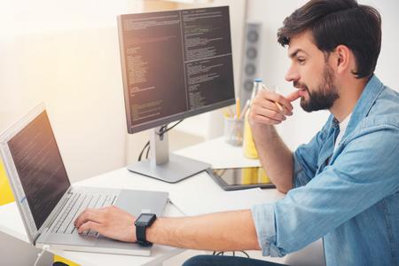 그것에 대해 생각. 노트북에 작업 하 고 사무실에 앉아 코딩하는 젊은 집중 된 프로그래머를 기쁘게 생각합니다. 스톡 콘텐츠