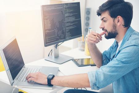 Haberlo hecho. hombre ambicioso concentrado joven que trabaja en una oficina como programador mientras que la codificación y la escritura de un programa