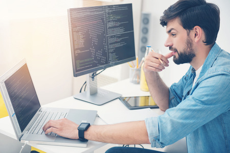 Have it done. Young concentrated ambitious man working in an office as programmer while coding and writing a program Banco de Imagens - 64097234