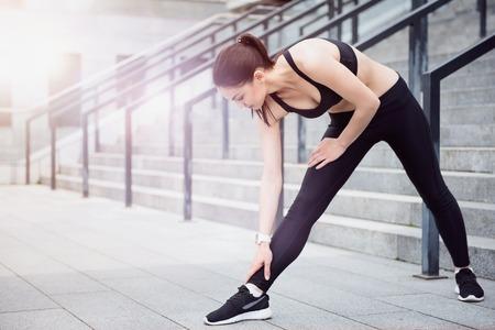 ropa deportiva: Manera de mantenerse en forma. Bastante joven flexible, que lleva una ropa deportiva y haciendo ejercicios de estiramiento a la espera de la formación.