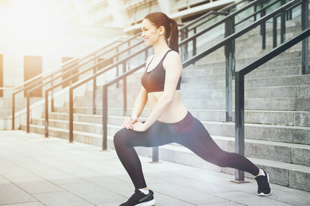 lunges: Joyful exercise. Beautiful young woman smiling and stretching her legs while exercising in an urban environment.