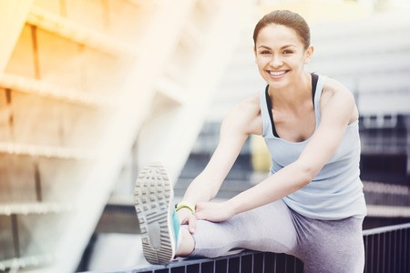 surroundings: Happy fitness. Beautiful slim cheerful woman smiling and exercising by stretching in urban surroundings. Stock Photo