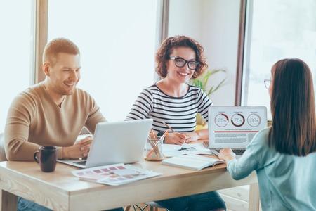 diligente: trabajadores diligentes. Agradables colegas positivos encantados sentado en la mesa y computadoras portátiles mientras se trabaja en la oficina