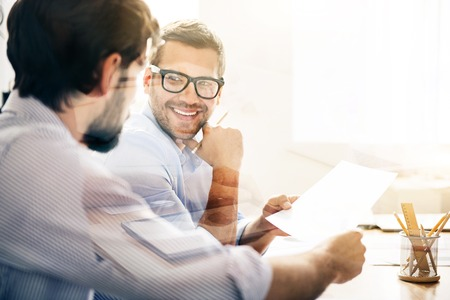 new contract: New solutions. Smiling bearded businessman wearing glasses is giving new contract to his business partner on white light background.