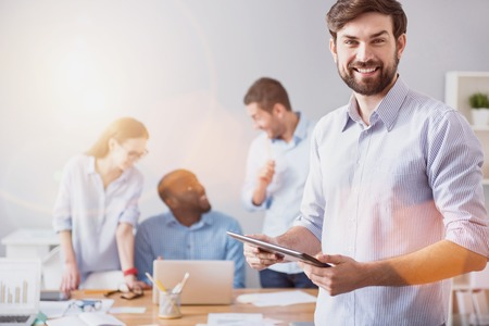 Développement de travail Jeune homme barbu souriant debout sur fond de collègues de travail avec tablette dans le bureau de la lumière. Banque d'images - 64095034