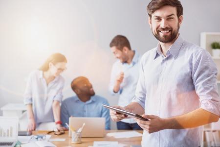 Desarrollo de trabajo. Hombre barbudo sonriente joven que se coloca en el fondo de colegas de trabajo con la tableta en oficina ligera.
