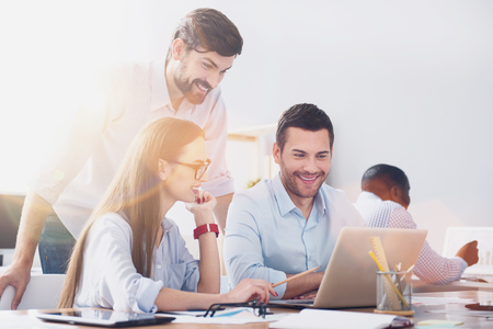 Happy workers. Picture of young office workers sitting with laptop at desk and man standing behind them. Stock Photo