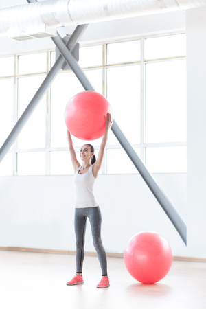 staying fit: Staying fit. Cheerful confident slim woman standing in a gym and holding a fitness ball up while doing a physical exercise