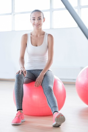 well built: Pleasant relaxation. Good looking cheerful well built woman sitting on a pink fitness ball and smiling while resting