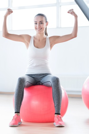 well built: Strong and confident. Happy well built strong woman holding her hands up and showing her muscles while sitting on the ball
