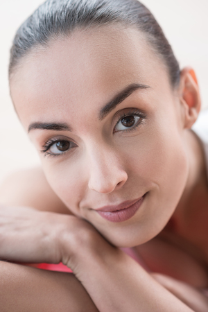 brown  eyed: Beautiful face. Pleasant brown eyed young woman looking at you and smiling while resting her face on the hand