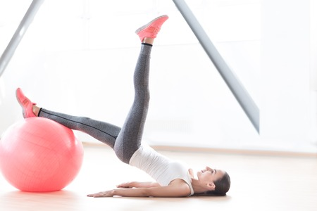 well built: Fitness exercise. Well built slender young woman resting one leg on a fitness ball and holding the second one up while lying on the floor