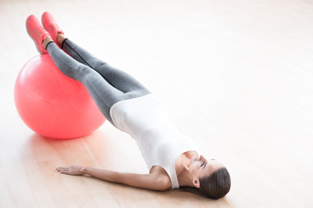 well built: Having a workout. Attractive slim well built woman resting her legs on a fitness ball and holding her body up while having fitness training