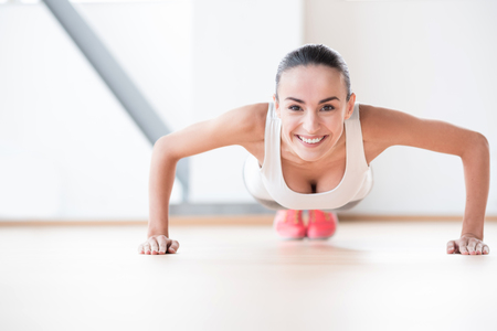 pleasurable: Pleasurable workout. Happy nice young woman looking at you and smiling while doing push ups