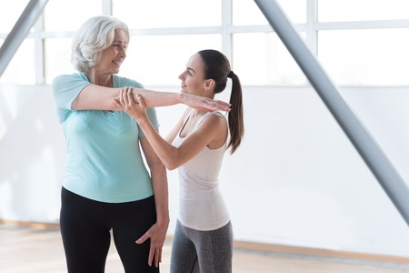 well built: Staying fit. Optimistic delighted well built women standing together and looking at each other while having a workout Stock Photo