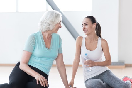 pleasurable: Pleasurable relaxation. Good looking optimistic slim women sitting together on the floor and looking at each other while resting during a fitness workout