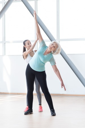 well built: Having aerobics classes. Well built serious confident woman stretching out her hands and bending to the left while training in a fitness club Stock Photo