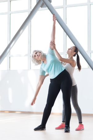 stretch out: Exercising in a fitness club. Pleasant confident persistent woman bending to the right and stretching out her arms while standing near the coach