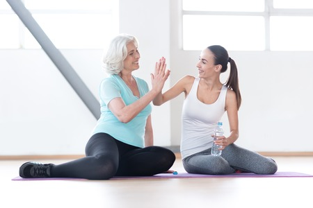 give me five: Give me high five. Cheerful emotional well built women holding their arms up and doing high five while sitting next to each other Stock Photo