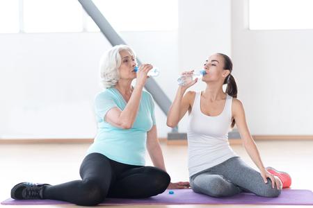 sediento: Prevenir la deshidratación. Buena pinta la celebración de botellas de plástico y agua potable sed mujer agradable mientras está sentado en una sala de gimnasia Foto de archivo