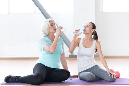 dehydration: Prevent dehydration. Good looking pleasant thirsty woman holding plastic bottles and drinking water while sitting in a gym hall Stock Photo