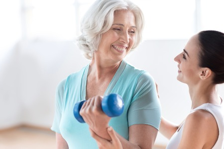 grey haired: Build up your body. Joyful good looking grey haired woman holding a blue dumbbell and smiling while looking at her coach Stock Photo