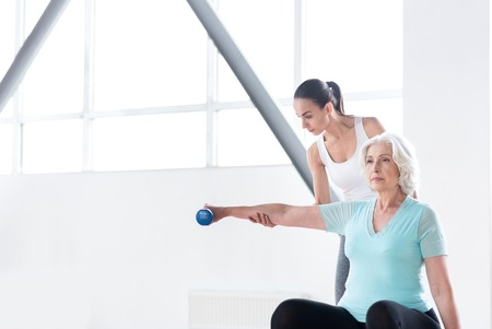 hard working woman: Concentrated on a physical activity. Nice pleasant hard working woman stretching out her hand and holding a dumbbell while having a workout in a fitness club