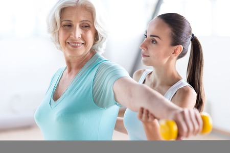 grey haired: Developing muscles. Positive confident grey haired woman stretching out her hand with a yellow dumbbell and looking at it while standing near the coach