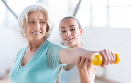 grey haired: You are never too old for sport. Good looking delighted grey haired woman holding a yellow dumbbell and smiling while training with a coach