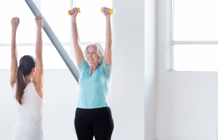 well built: Healthy way of life. Pleasant well built old woman standing opposite her fitness coach and holding her dumbbells up while repeating after her Stock Photo
