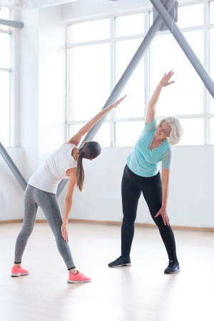 well built: Let us do it together. Nice optimistic well built women standing opposite each other and doing physical exercises while being in a fitness club