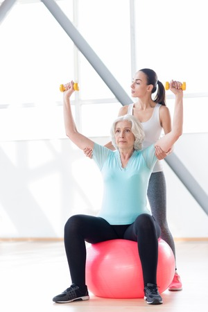 persistent: Serious attitude to the workout. Persistent confident active woman sitting on a fitness ball and raising her arms while holding dumbbells