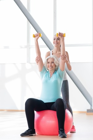grey haired: Positive attitude. Cheerful good looking grey haired woman holding her hands up and smiling while sitting on a fitness ball
