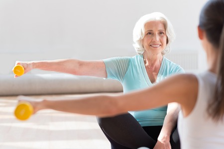 legged: Simultaneous movements. Pleasant happy active women sitting cross legged opposite each other and raising their hands while holding dumbbells