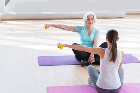 grey haired: Calmness and peace. Good looking peaceful grey haired woman sitting cross legged on a yoga mat opposite her coach and holding a yellow dumbbell