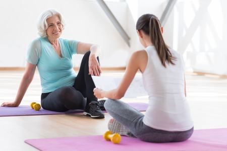 good looking woman: Enjoying their rest. Positive happy good looking woman sitting on a yoga mat and smiling while looking at the her coach
