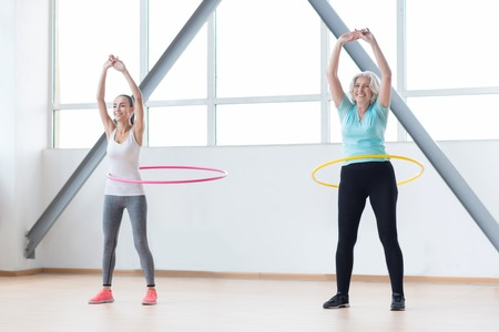 Making your waist thinner. Good looking energetic sporty women holding their hands up and smiling while rotating  hoops Stock Photo