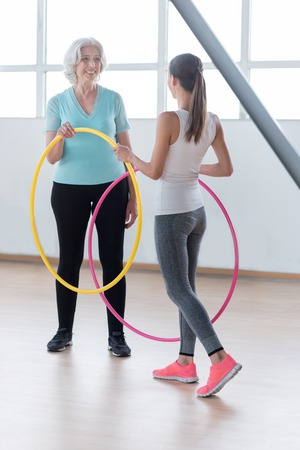 well built: Let us start exercising. Well built slim fitness coach holding  hoops and giving one of them to the woman while preparing to new exercises